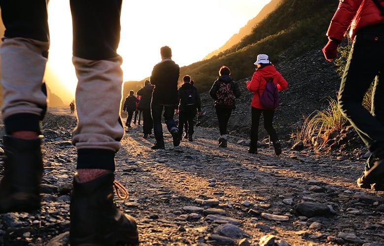 Varias personas caminando por el monte en un camino de tierra y piedras. Con mochilas y ropa de montaña.