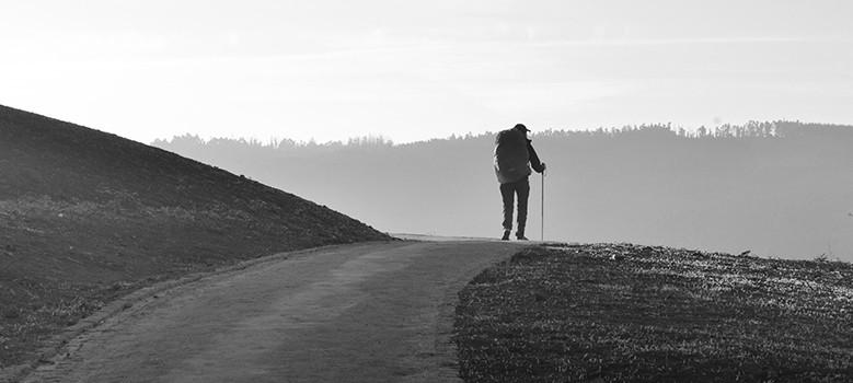 Hombre caminando en un camino con una mochila y un bastón