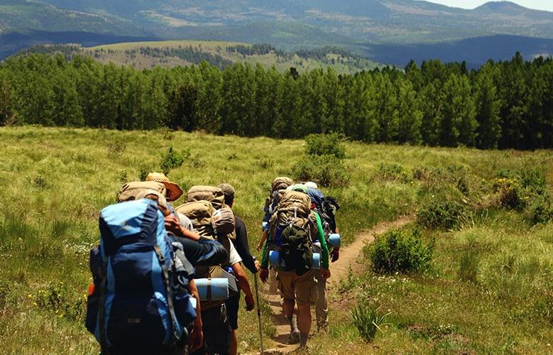 Grupo de Gente con mochilas paseando por el campo.