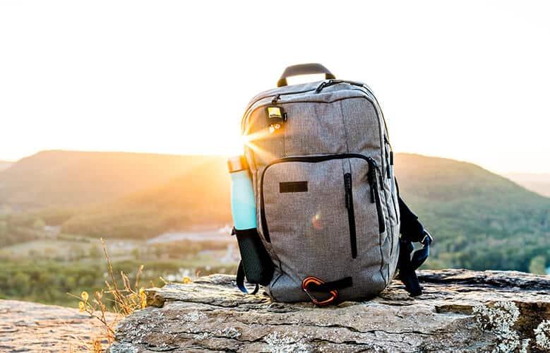 Mochila en el monte con una puesta de sol